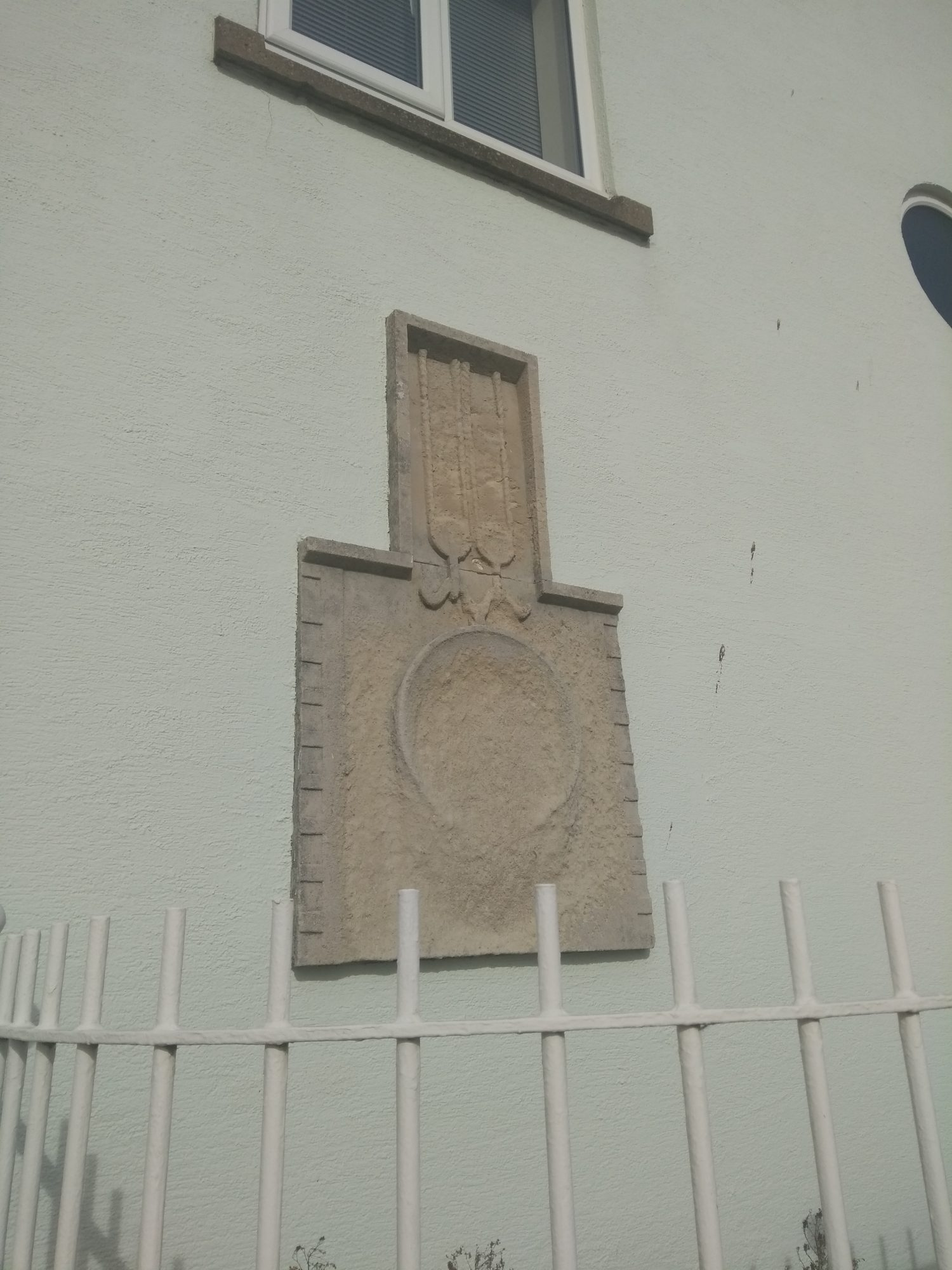 An eroded wall plaque in Swansea's Maritime Quarter.